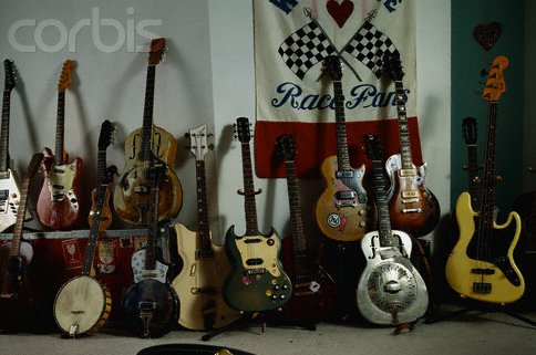 Chris's guitar collection:   Top (l to r): 1 - partial image of G-707, guitar synth; 2 - Fender Duosonic; 3 - Charango (Andean lute); 4 - National Triolian; 5 - Gibson Les Paul Jr; 6 -'52 or '53 Gibson Les Paul (originally a goldtop) Bottom (l to r):  1 - old Martin (either an old D-15, or possibly a 00-18 or 00 series); 2 - Bart Reiter 5-string banjo; 3 - National Resophonic 1133; 4 - Airline (Supro) Reso-glass short scale bass; 5 - Gibson Melody Maker ; 6 - Sunburst Gibson Les Paul Special; 7 - National Resophonic Style O; 8 - Fender Jazz Bass